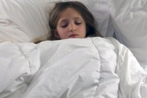 A run girl sleeping among a mountain of white blankets.