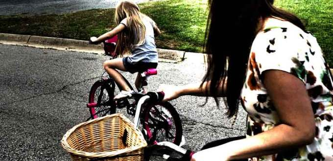 Mom and daughter riding bicycles together.