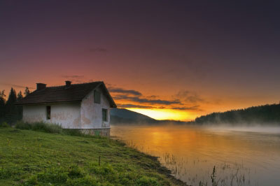 House on a lake with a sunset in the background.