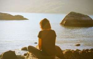 woman sitting next to lake