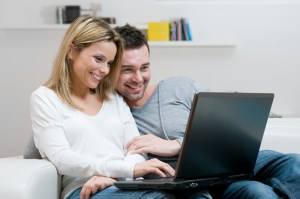 Happy couple talking on the computer during online marriage therapy | Texas marriage therapy | Online marriage counseling in Texas