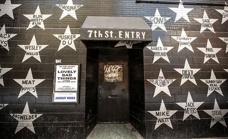 The entrance of 7th street entry in downtown Minneapolis, Minnesota, featuring a black brick wall with stars of artists who have performed here over the years.