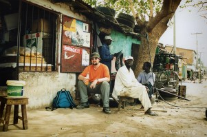 Miles waiting for yet another taxi tyre change (note inner tube behind me!), The Gambia, 2000