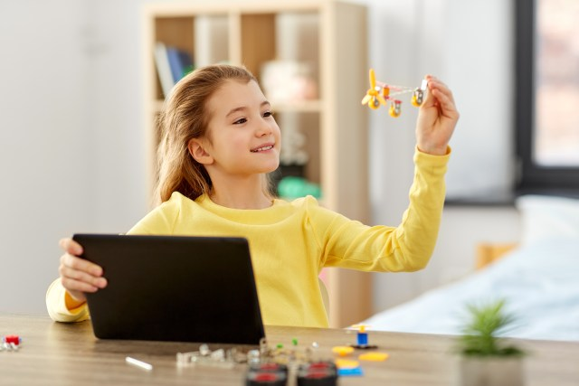 girl with tablet pc and robotics kit at home