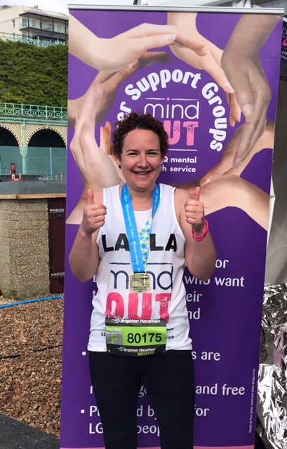 A smiling woman giving two thumbs up and wearing a medal for having just completed the Brighton Marathon 2018.