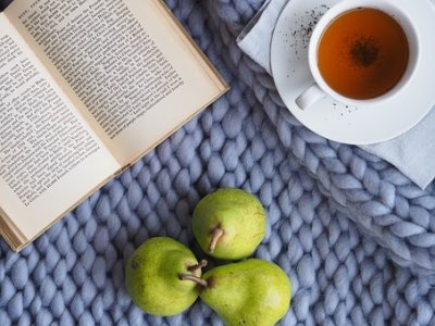 bird's eye view of an open book, a tea in a cup on a saucer, three pears, all placed on a blue-grey wool blanket