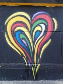 graffiti of heart in rainbow colours on a black wall