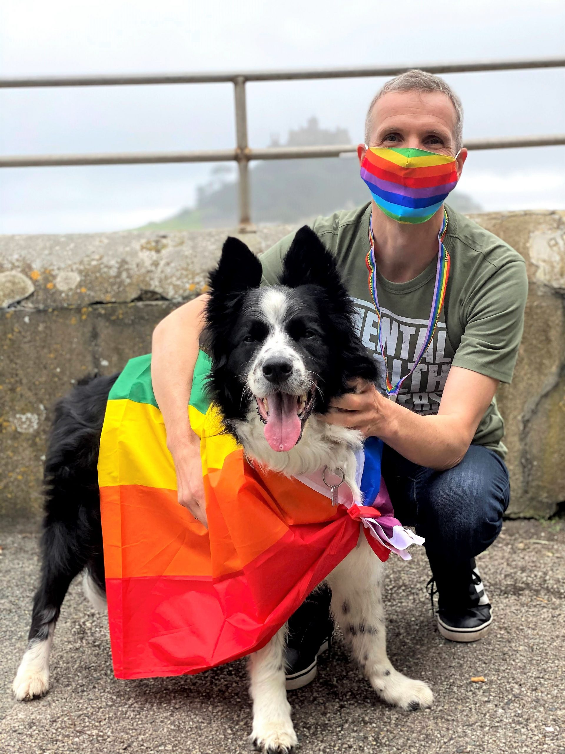 Colin, a MindOut volunteer, wearing a rainbow mask and next to a dog wearing a rainbow flag