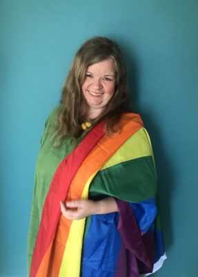White woman with long brown hair, wearing the pride flag on her shoulder