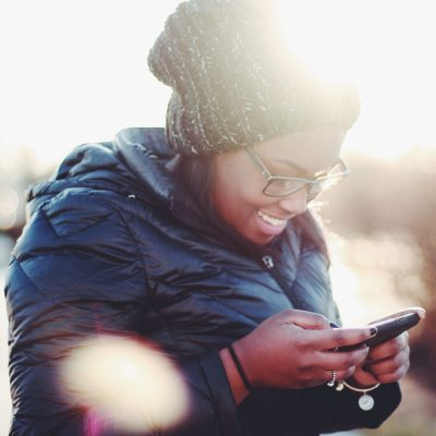 Black person with long hair and glasses smiling and looking down at their phone. they are outside and wearing a warm jacket and wooly hat.