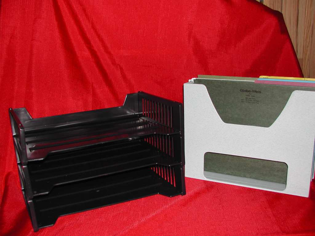 3 black stackable plastic trays for filing and a white desktopper holding file folders for filing paperwork