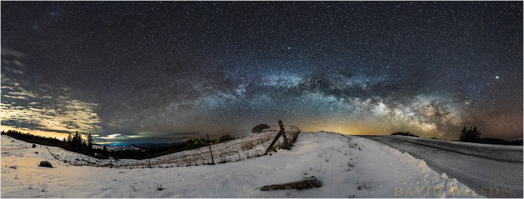 Snowy nighttime panorama beneath the Milky Way along a country road.