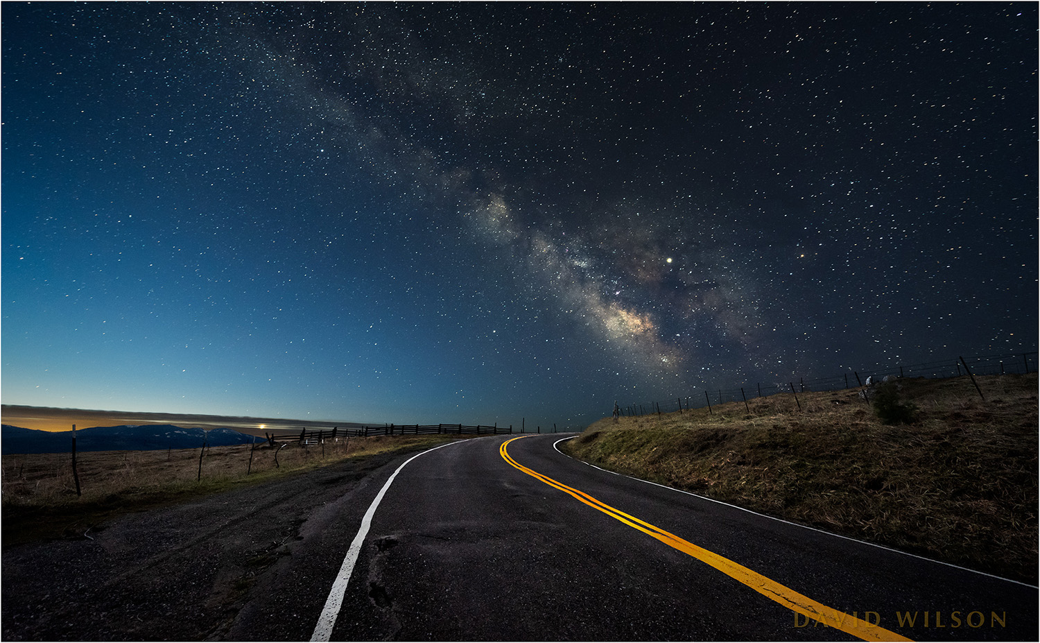 A bend in a rural road leads toward the Milky Way