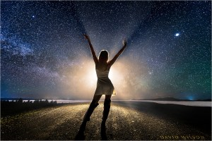 Silhouette on country road celebrates the cosmos