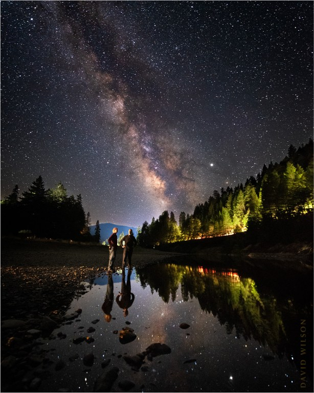 Two people stand amid reflections of the Milky Way along the South Fork Eel River.
