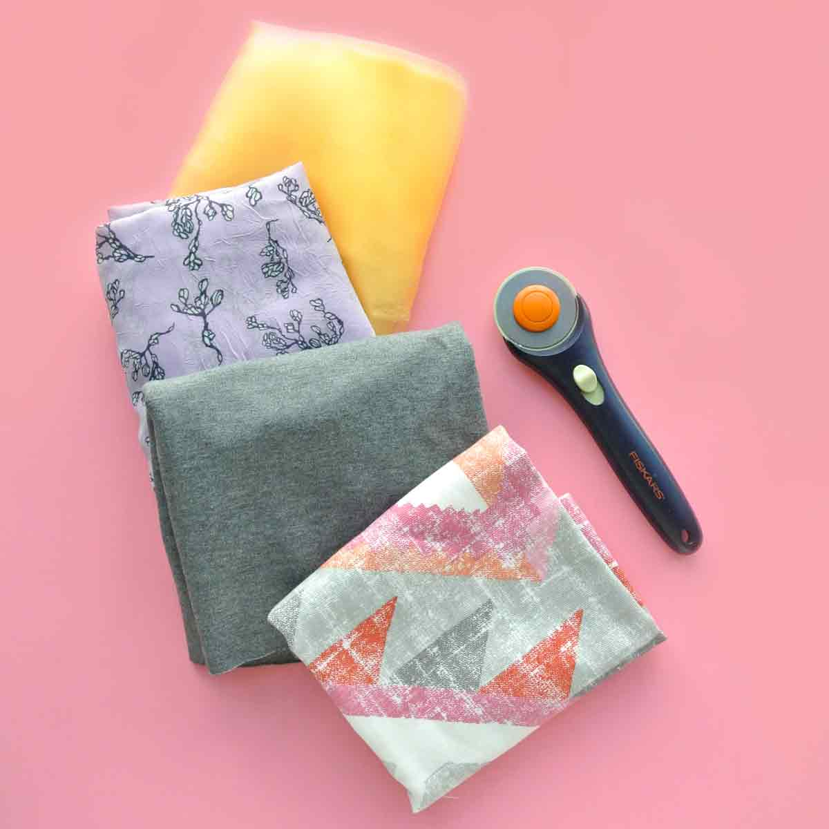 Rotary Cutter Vs Scissors. Shows Rotary cutter with 4 types of fabrics that it's good for cutting (tulle, chiffon, knit, cotton)