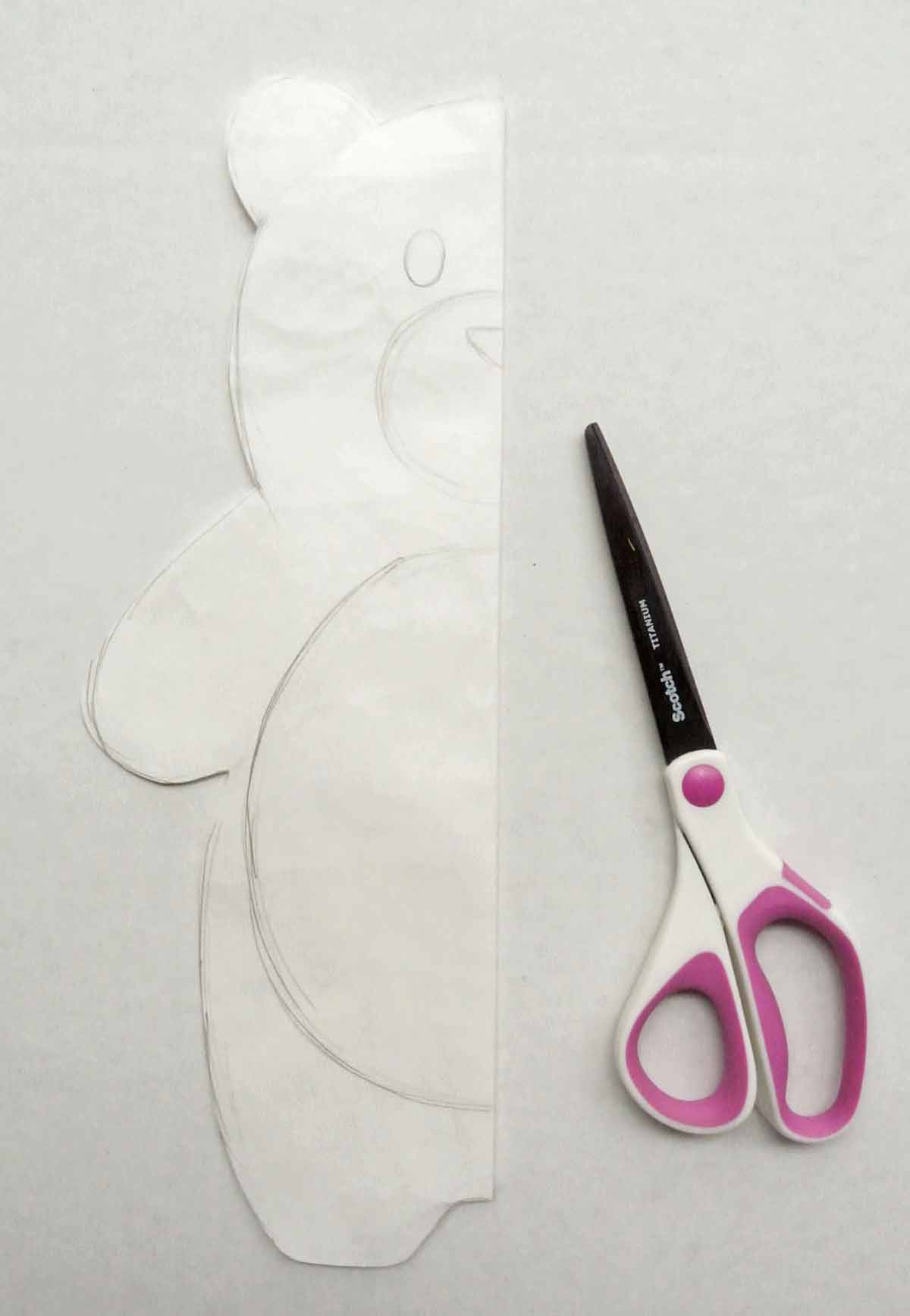 Shows Bear Plush Pattern Folded in half with scissors. How to Make Plushie Tutorial