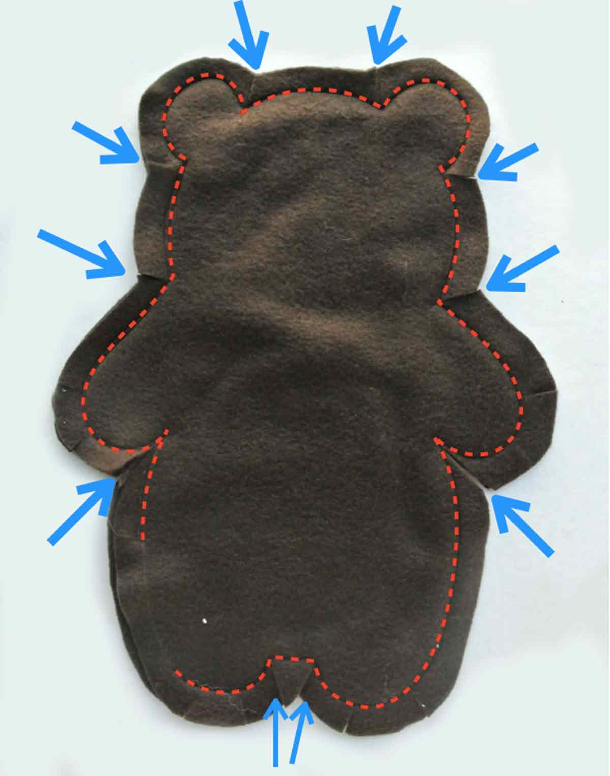 Bear Plushie with red dotted lines indicating where to sew and blue arrows indicating where to clip curves. How to Make Plushie Tutorial
