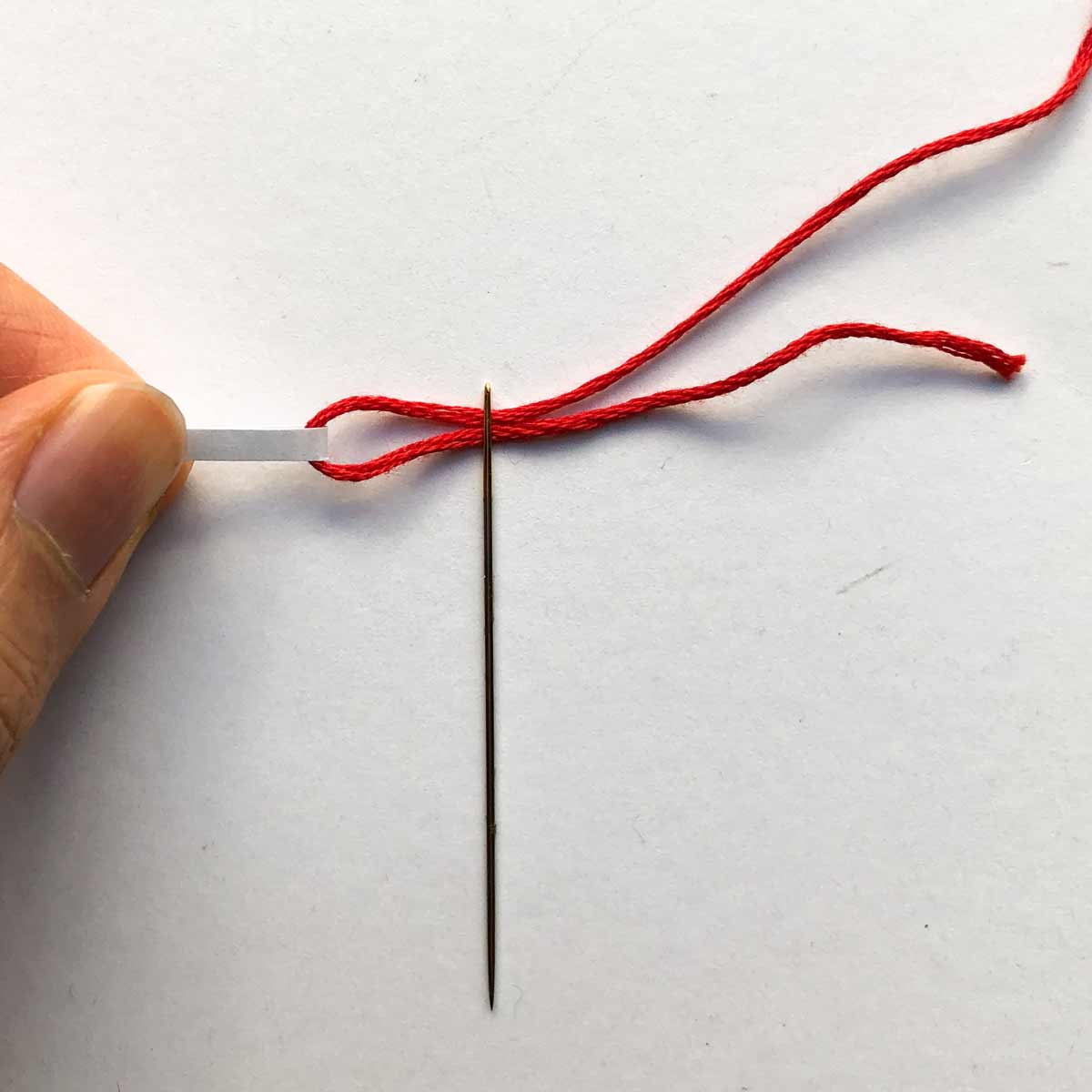 Pulling thread through eye of needle