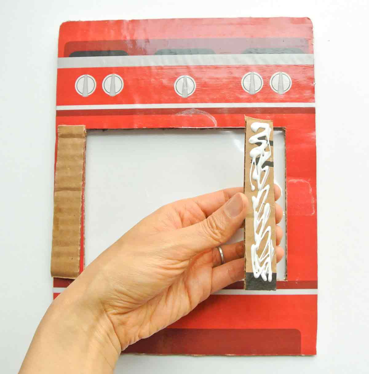 Gluing side pieces to cardboard oven. Toddler Cookie Counting activity free printable