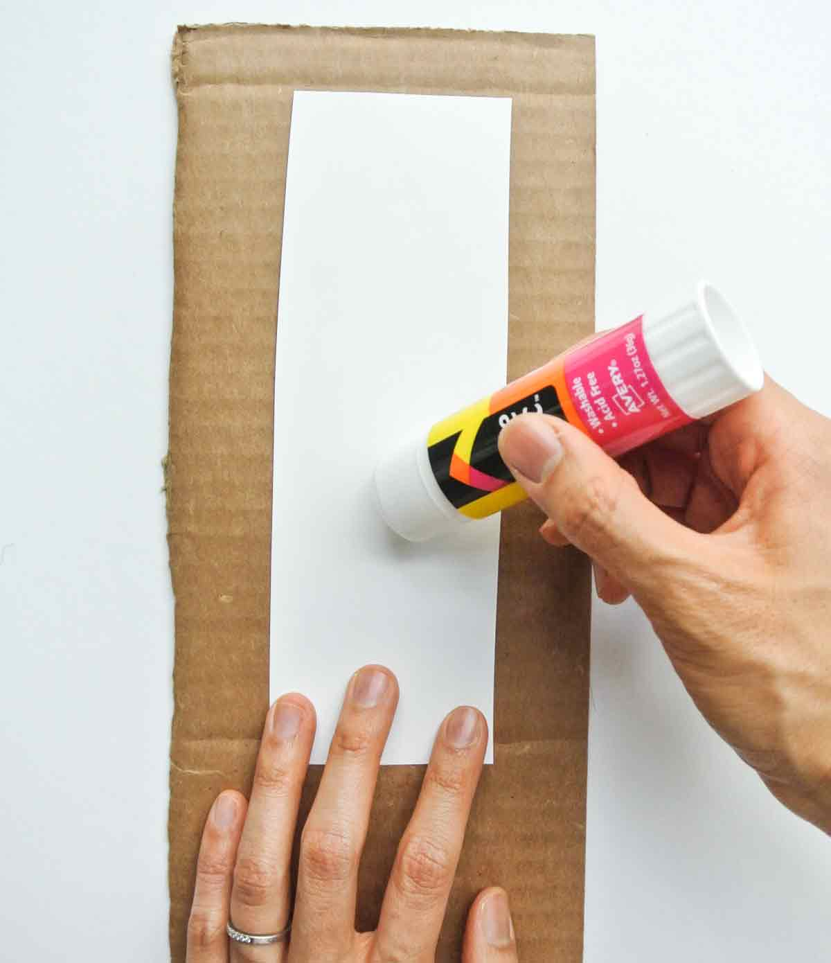 applying gluestick to back of free printable. Toddler cookie counting activity