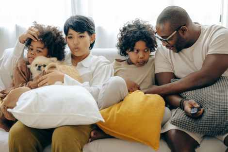 multiethnic family resting together on sofa with dog in living room