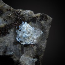 Plagioclase var. labradorite (Ca,Na)[Al(Al,Si)Si2O8] with blue labradorescence in gabbro/anorthosite; Wolibórz (Volpersdorf), Kłodzko District, Lower Silesia (Dolnośląskie), Poland; crystal 6 x 5 mm