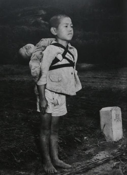 Menino carregando seu irmão morto, provavelmente vítima de radiação, em Nagasaki, em 1945.