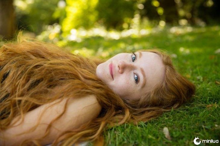 mulher de cabelos deitado na grama