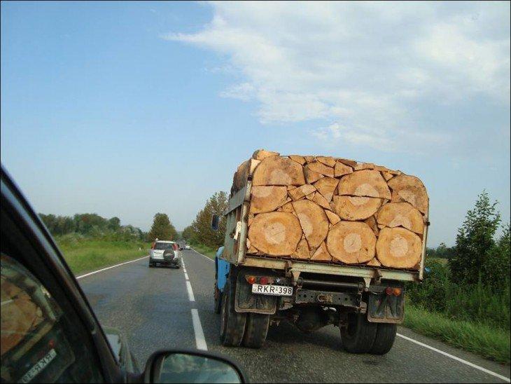 Caminhão em uma estrada com pedaços de madeira em perfeita ordem