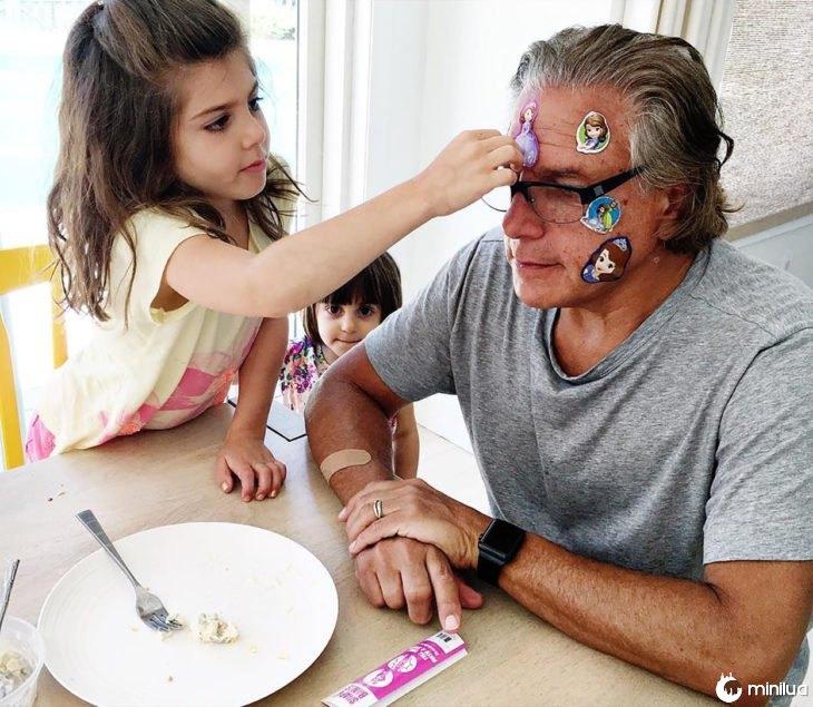menina batendo um adesivo na cabeça de um homem