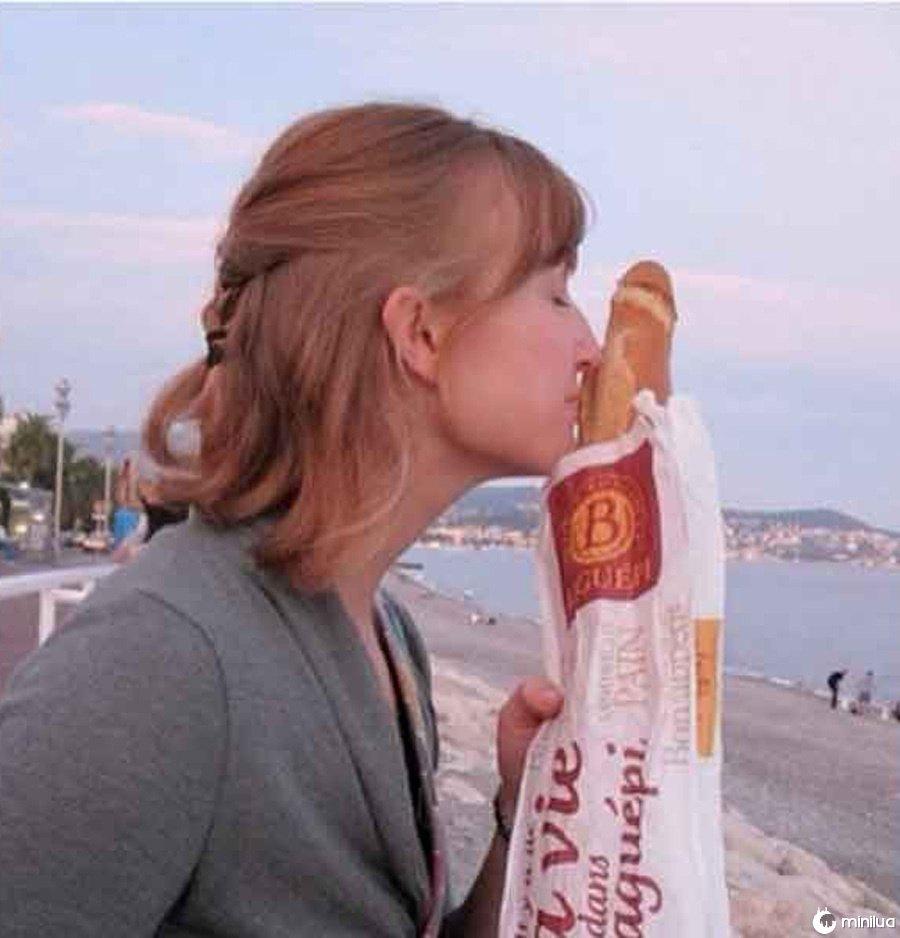 Ela está cheirando o pão francês fresco.
