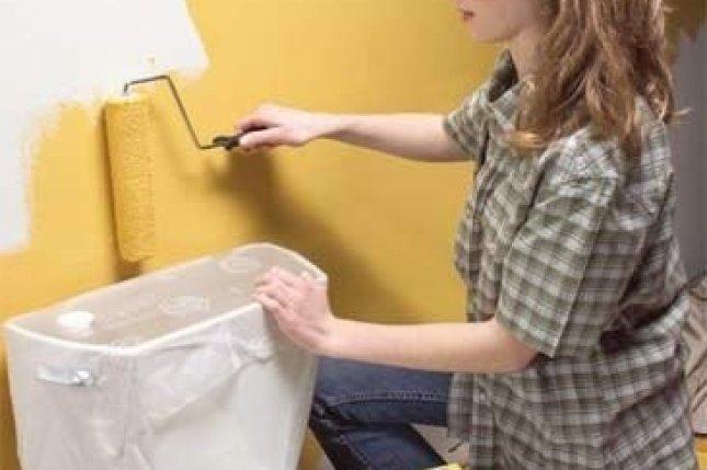 ajoelhado mulher pintando uma parede amarela