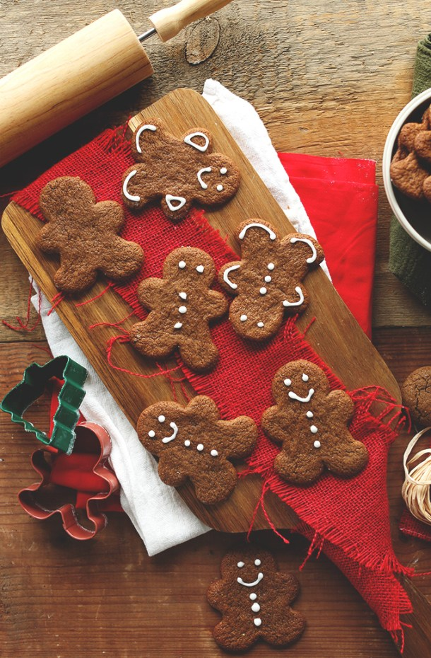 Partially decorated Vegan Gluten-Free Gingerbread Cookies on a cutting board