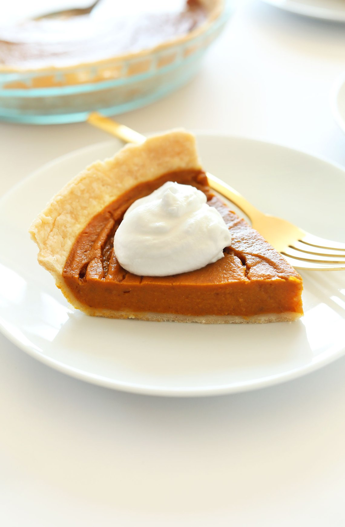 Small plate with a slice of Vegan Gluten-Free Pumpkin Pie topped with coconut whipped cream
