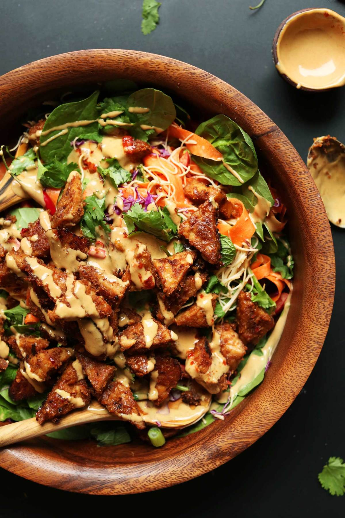 Wood bowl filled with gluten-free vegan Thai Salad with Marinated Peanut Tempeh
