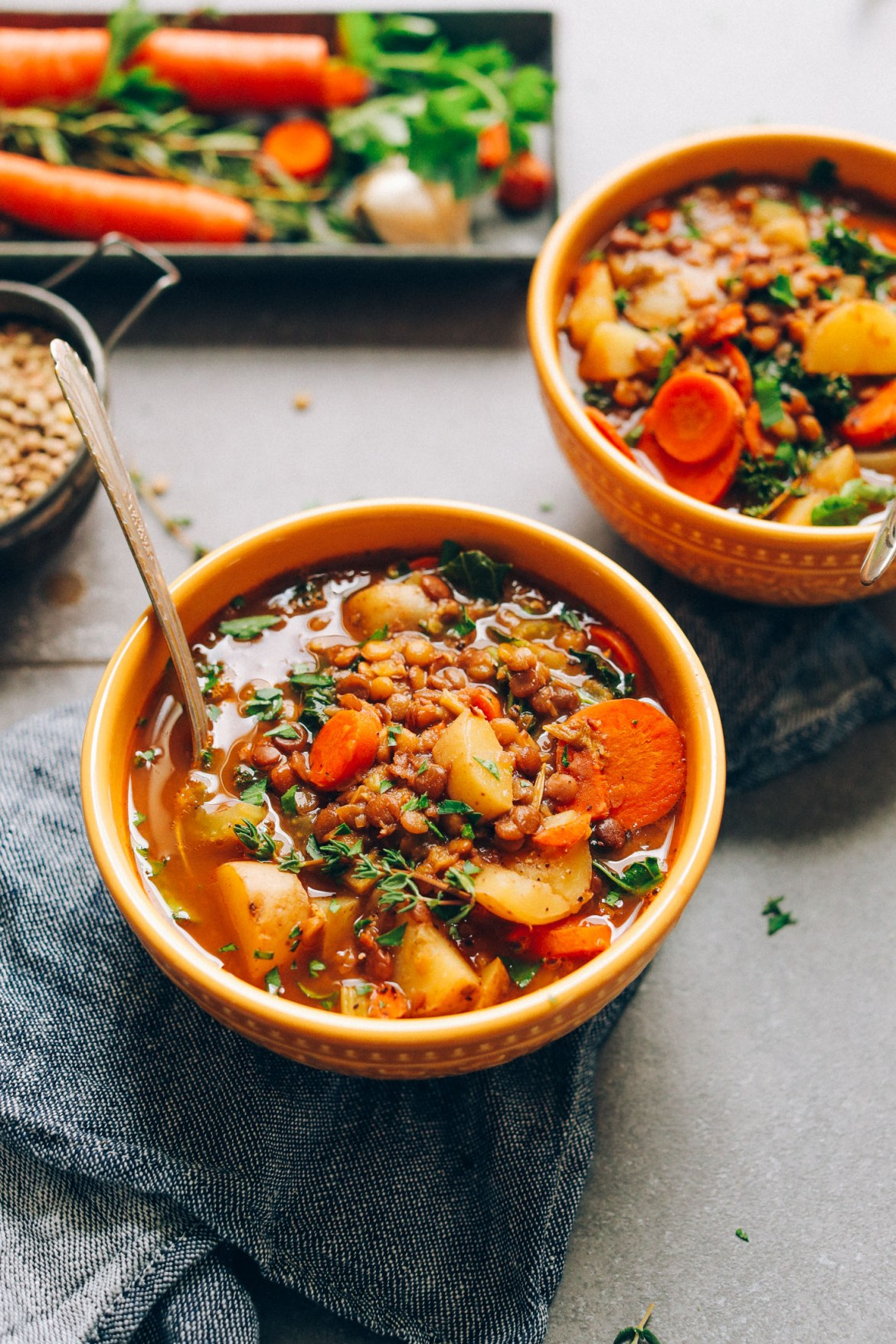 Bowl of our Everyday Lentil Soup recipe garnished with sprigs of fresh thyme