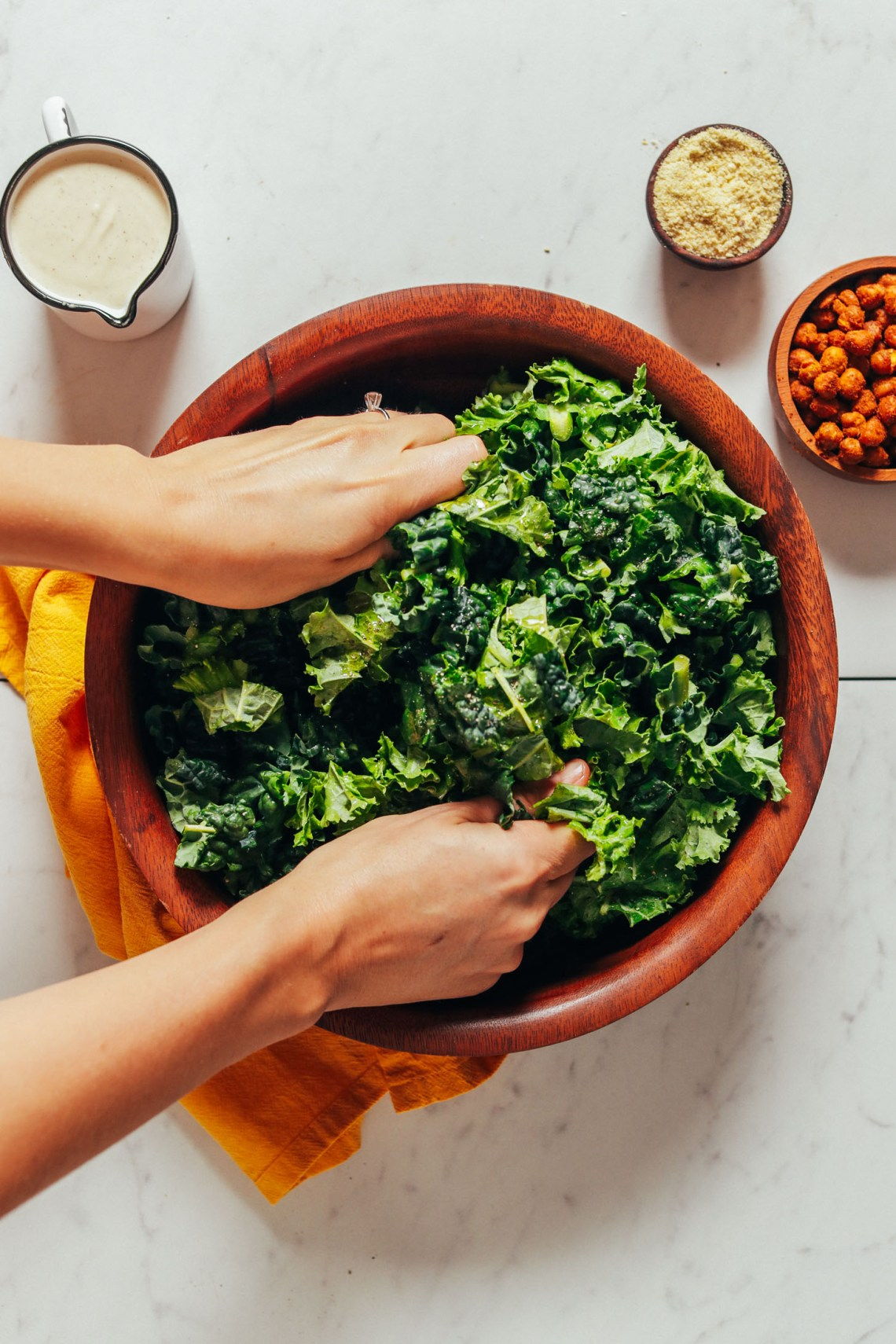 Using our hands to massage a bowl of kale for Chickpea Kale Caesar Salad