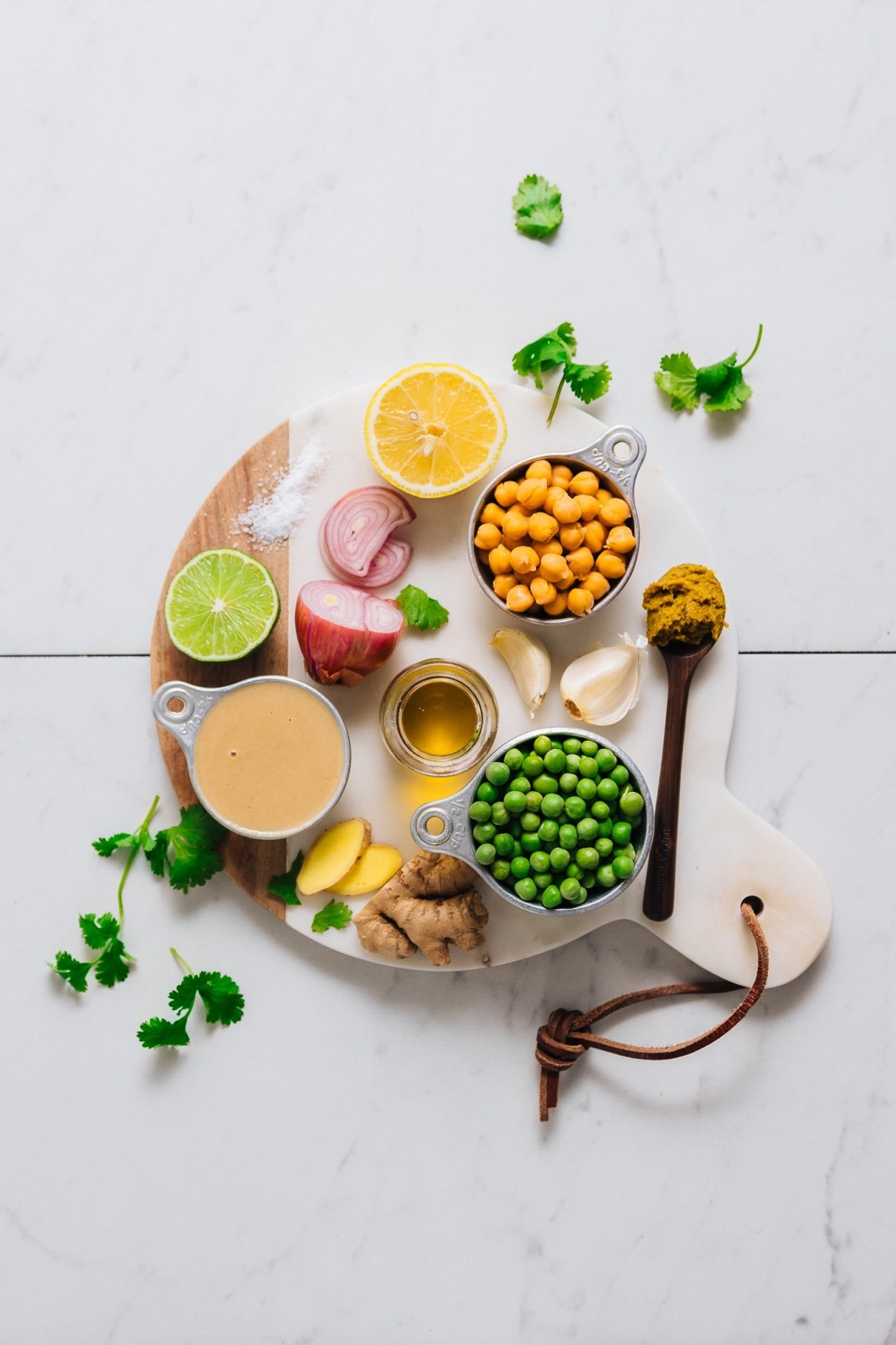 Wood and marble cutting board filled with ingredients for making our flavorful Green Pea Curry Hummus recipe