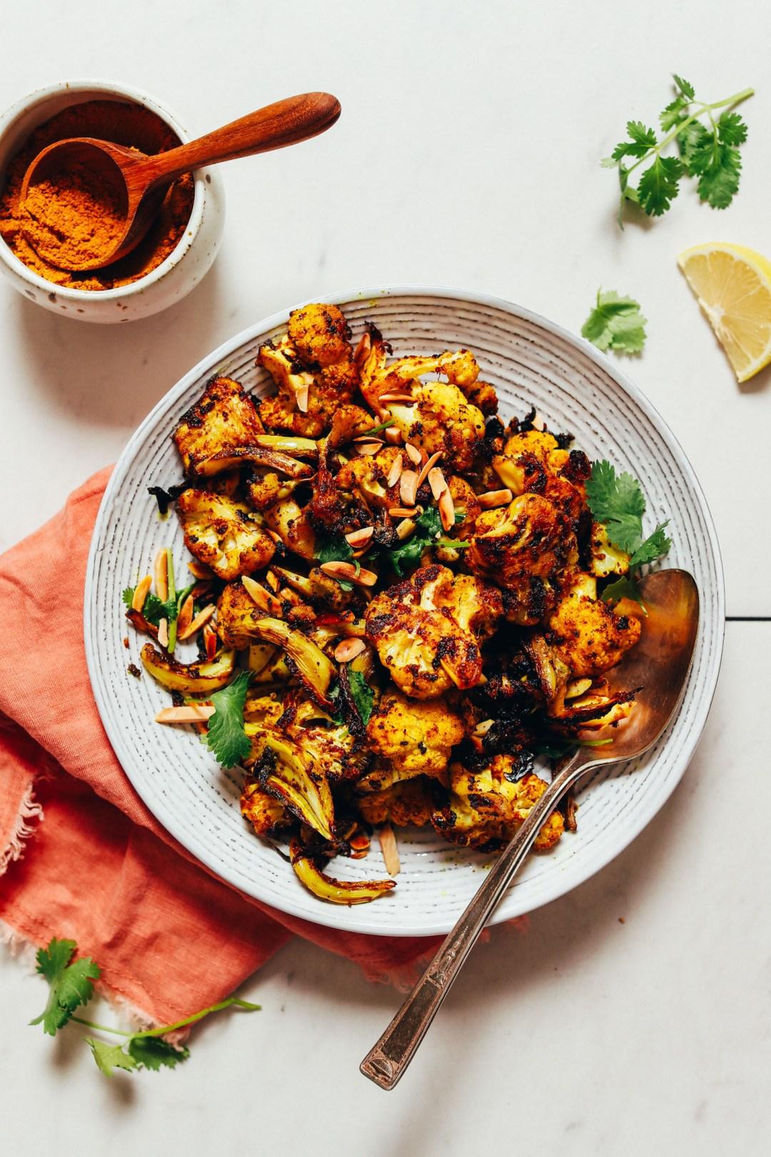 Curry en polvo, rodaja de limón y cilantro junto a un tazón de coliflor crujiente rápida