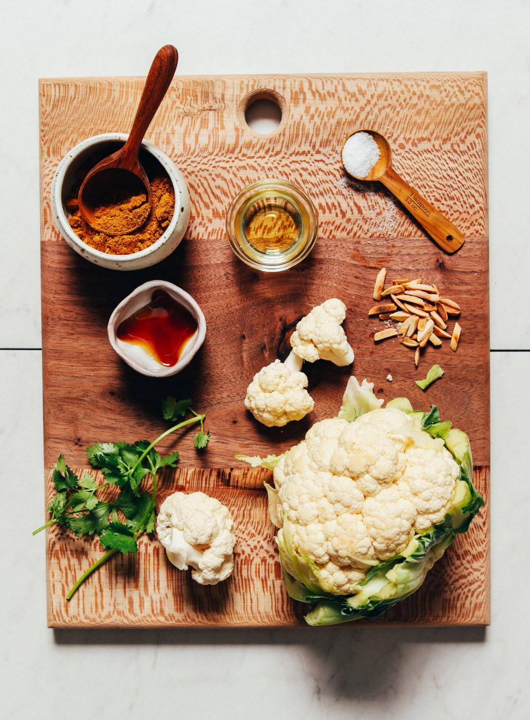 Tabla de cortar de madera con ingredientes para hacer nuestra receta de coliflor crujiente rápida