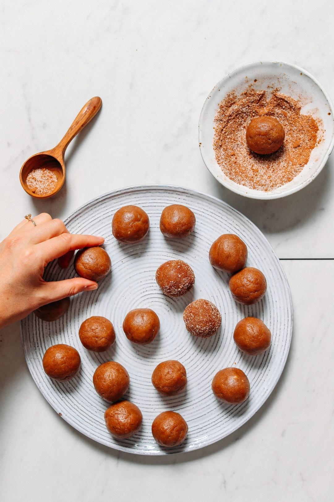 Plato de GF Vegan Snickerdoodle Cookies con algunas enrolladas en la capa de azúcar de canela