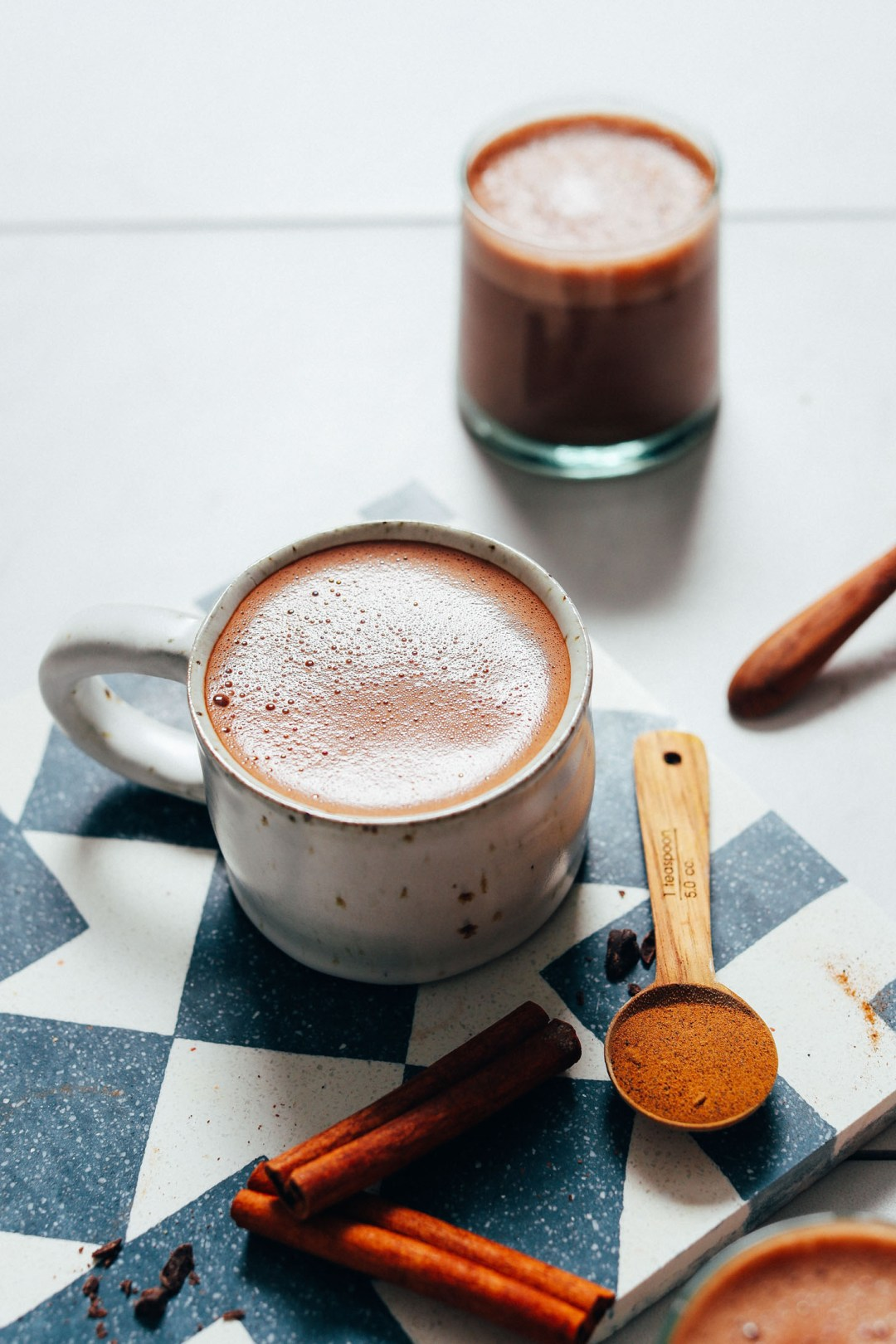 Taza y vaso de chocolate caliente vegano con adaptógenos y canela