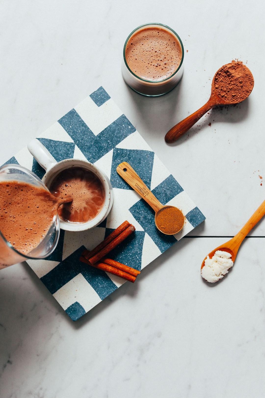 Verter una taza de nuestra receta de chocolate caliente adaptogénico sin lácteos junto con los ingredientes utilizados para prepararla