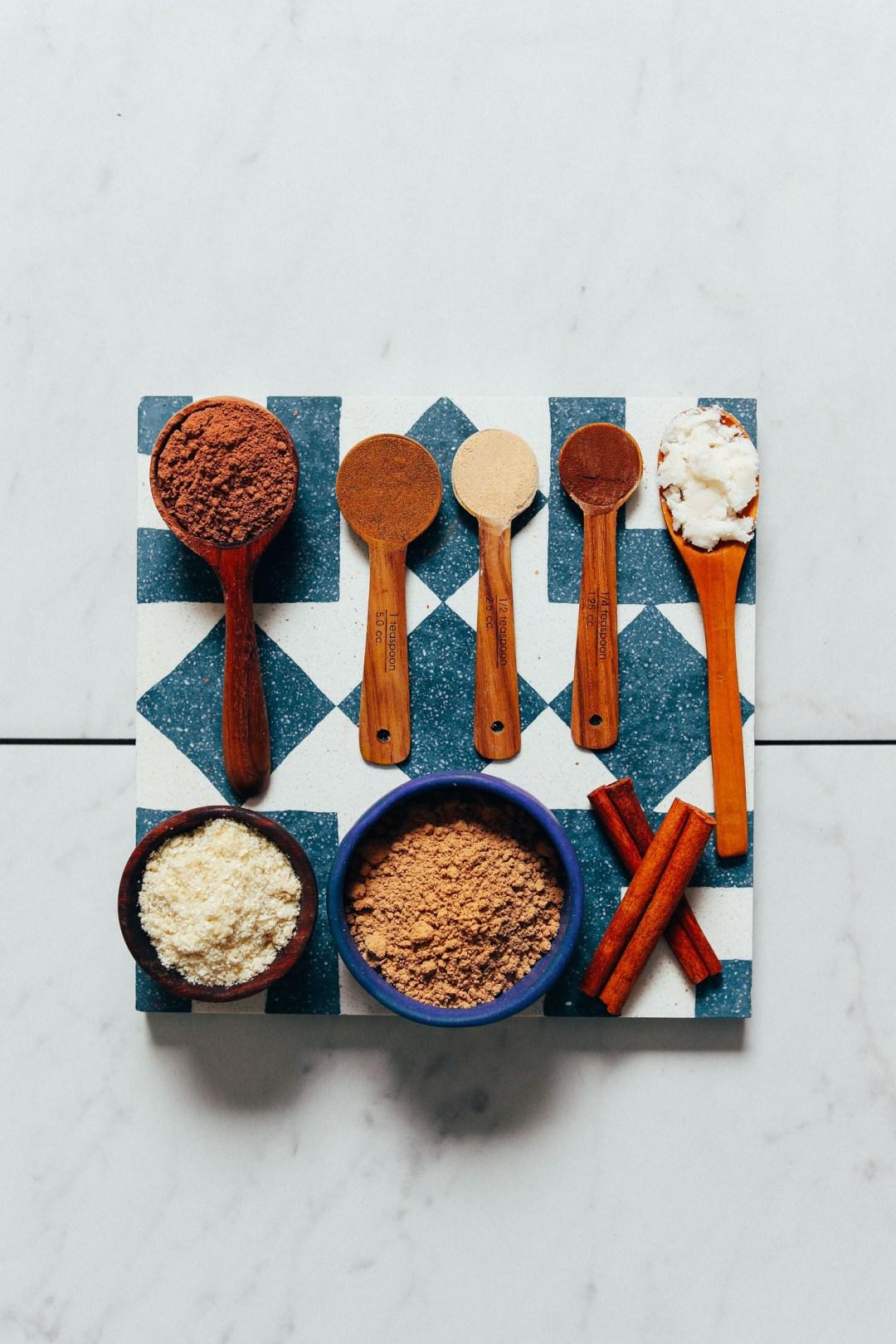 Cucharadas y cuencos de cacao en polvo, Ashwagandha, polvo de hongo reishi, maca, mantequilla de coco y canela para hacer nuestra receta de chocolate caliente con adaptógenos