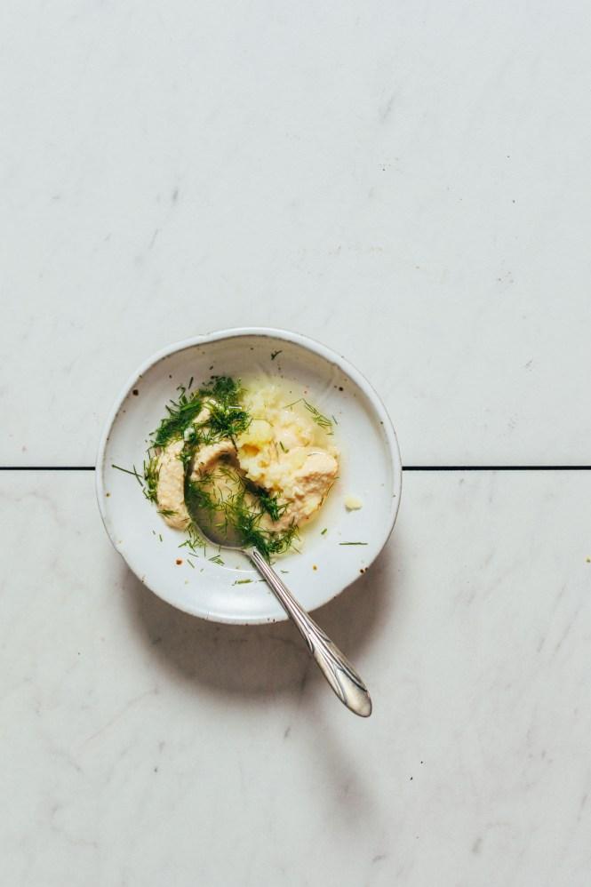 Bowl of hummus, dill, garlic, and lemon