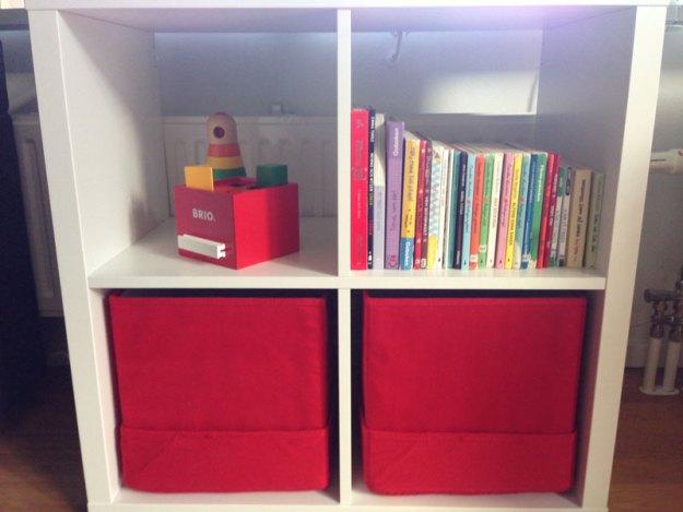 Barnens bokhylla med såväl böcker som lådor för leksaker.