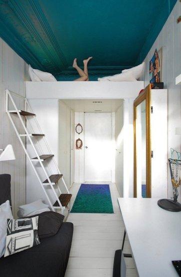 Una cama alta se construye discretamente a través de una puerta, también creando un inteligente armario ropero estrecho.