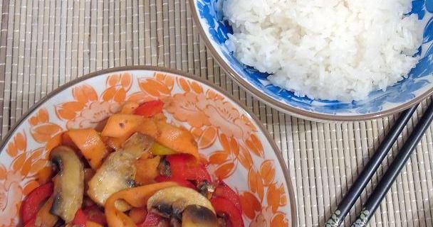 Reis und Gemüse in einer Schale auf Bambusmatte mit Essstäbchen