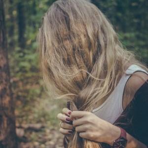 Blonde Frau flechtet Haare ohne Haargummi